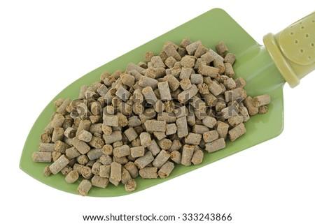 A shovel full of compressed Organic Animal-based Fertilizer Pellets isolated on white - stock photo