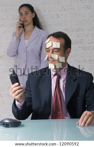 A show of a young businesswoman and middle-aged businessman talking on phones.  The man's face is covered in sticky-notes. - stock photo