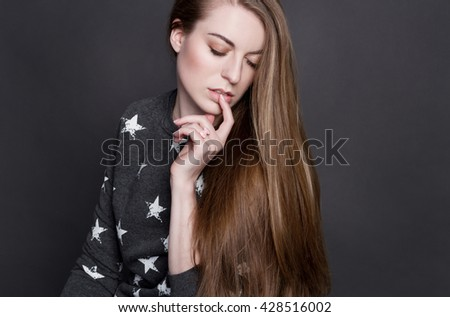 A shy young blonde girl in a gray sweater with printed stars. She sensually touches her lips with her finger. She has luxurious shiny hair, clear skin and a delicate blush. - stock photo