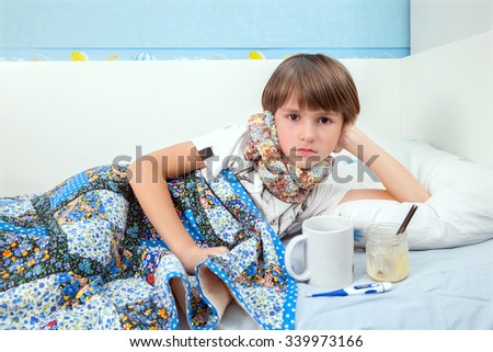 A sick boy is resting in bed with cup of hot beverage and honey - stock photo