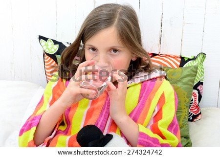 a sick girl drinking a glass of water in her bed - stock photo