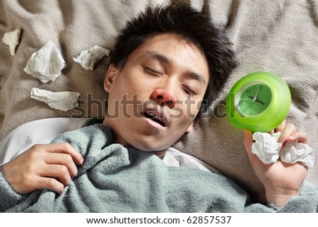 A sick male sleeping with clock near him