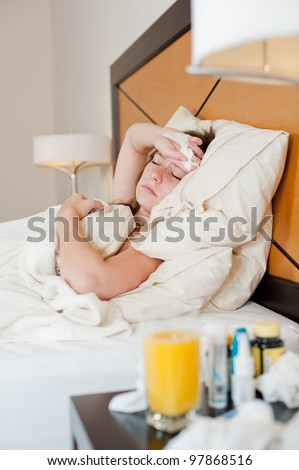 A sick young lady in bed, lying back against cushions with a tissue in her hand. Some medicine and orange juice out of focus in front. - stock photo