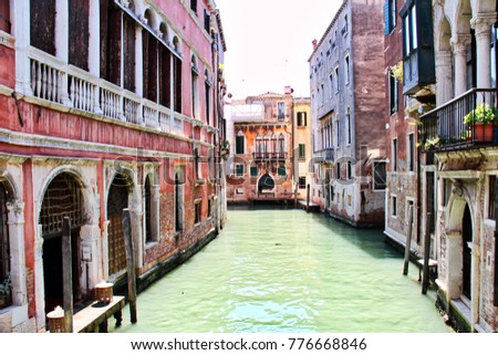 A side canal in daylight in Venice, Italy.