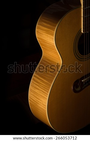 A side lit acoustic guitar body on a black background.