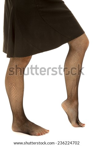 A side shot close up of a woman legs in black fishnet stockings and a black skirt. - stock photo