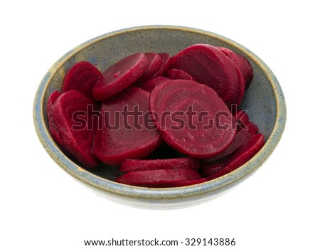 A side view of a colorful bowl of sliced beets in a gray speckled bowl on a white background. - stock photo