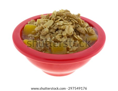 A side view of a red bowl of diced peaches in syrup topped with crunchy oats and brown sugar. - stock photo