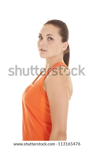 A side view of a woman in her orange workout top looking at camera - stock photo