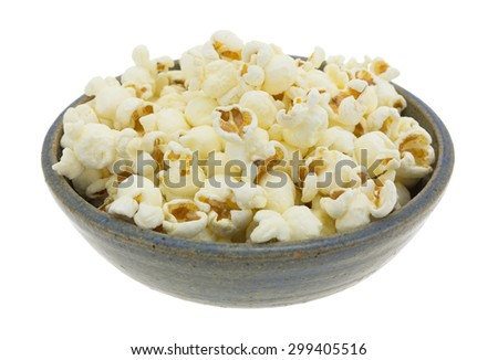 A side view of crunchy and delicious white cheddar cheese popcorn in a gray ceramic bowl. - stock photo