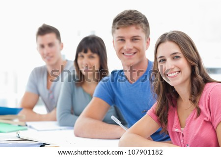 A side view shot of four students looking at the camera and their bodies turned towards it - stock photo