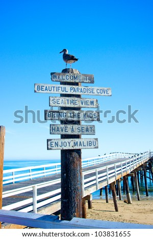A sign and a seagull welcome visitors to the pier at Malibu Beach in California.