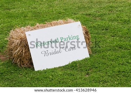 A sign and haybale indicating reserved parking for bridal cars. - stock photo