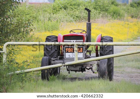 A sign hangs on the tractor's front grill seeking buyers/Tractor for Sale/A sign hangs on the tractor's front grill seeking buyers.  - stock photo
