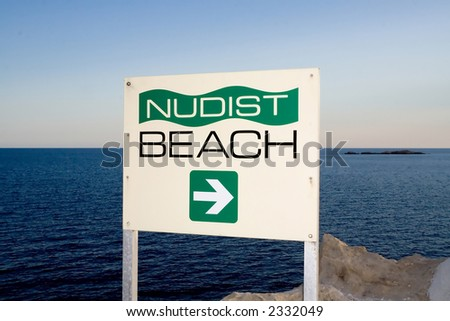 A sign indicating the direction of a nudist beach with the Adriatic Sea in the backgroung - stock photo