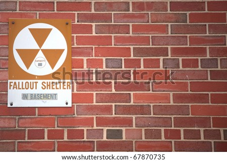 A sign indicating the whereabouts of a fallout shelter. - stock photo