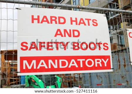 A sign is posted outside a construction site requiring hard hats and safety boots/Construction Site Safety Sign/A sign is posted outside a construction site requiring hard hats and safety boots.