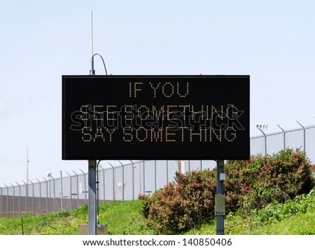 A sign near a major airport urges citizens to report suspicious activity. - stock photo