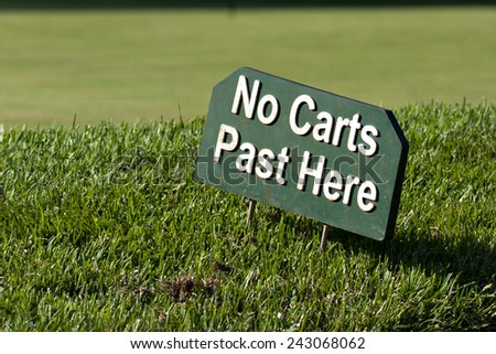 A sign on a golf course warns golfers not to drive their carts onto a green. - stock photo