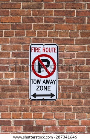 A sign on a red brick wall warns of no parking,fire route and tow away zone outside a building. - stock photo