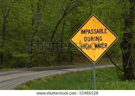 a sign on a secondary road in the foothills of the Ozark Mountains in southeast Missouri warning of an impassable road in event of high water - stock photo