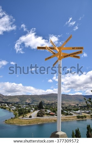 A sign post and Cromwell township across the Kawarau River..