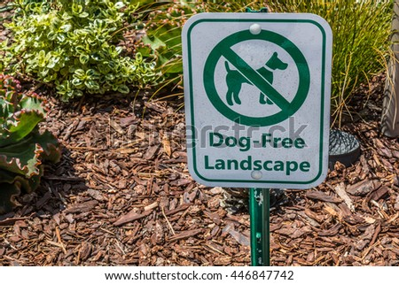 A sign posted to prohibit access of dogs on the landscaping. - stock photo