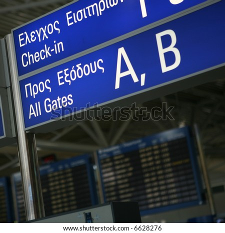 A sign to the boarding gates in English and Greek at Eleftherios Venizelos International Airport, Athens. The flight departures information board is out of focus in the background - stock photo