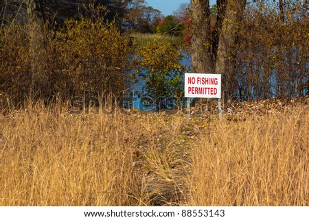 """A sign warning of """"No Fishing Permitted"""" in a natural setting - stock photo"""
