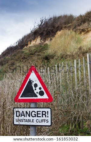 A sign warning of unstable cliffs at Dunwich, Suffolk, UK - stock photo