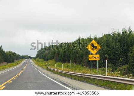 A sign warning people that moose may walk across the road - stock photo