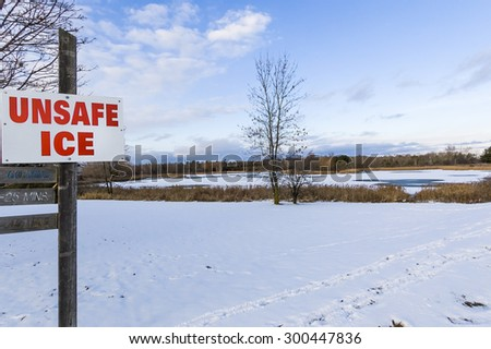 A sign warns of unsafe ice on the pond in the distance. - stock photo