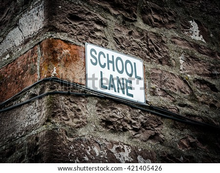 A Sign With School Lane On The Side Of A Building In The UK - stock photo