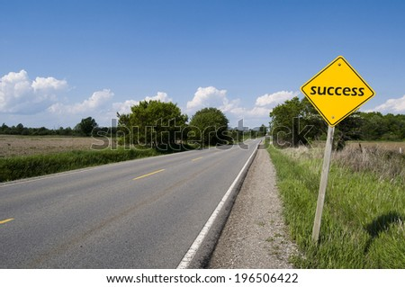 A sign with the word 'success' on the side of a deserted road. - stock photo