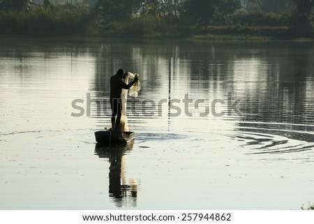 A silhouette fisherman throw a net to catch a fish in a river