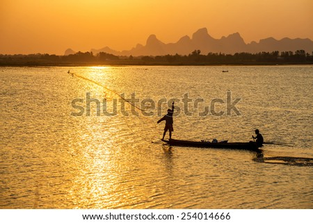 A silhouette fisherman throw a net to catch a fish in a river in the sunset time - stock photo