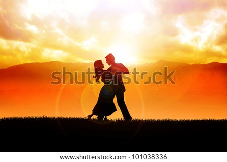 A silhouette illustration of a couple dancing during sunrise - stock photo
