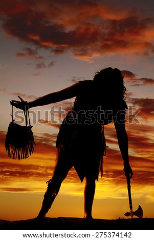 A silhouette of a cave woman in her dress with a hatchet.