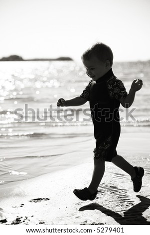 A Silhouette of a child running at the beach - stock photo