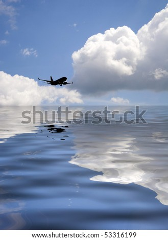 A silhouette of a commercial passenger plane flying over the water. - stock photo