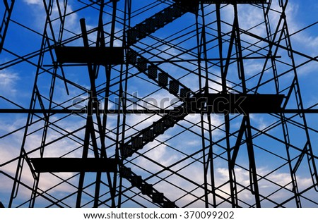 A silhouette of a construction scaffolding stairs a blue cloudy sky.