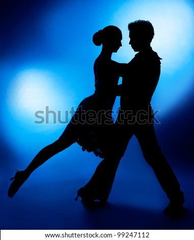 A silhouette of a couple dancing against blue studio background - stock photo