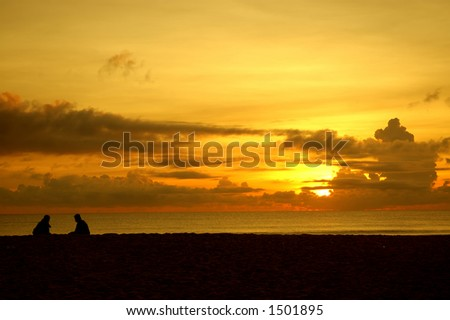 A silhouette of a couple talking by the beach at sunset.