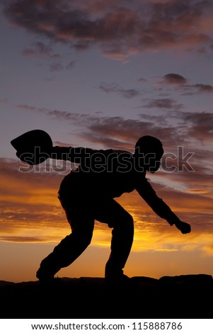 A silhouette of a cowboy bending low and holding on to his hat. - stock photo