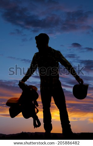A silhouette of a cowboy holding on to his saddle and hat. - stock photo