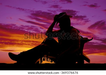 a silhouette of a cowboy leaning back against a saddle. - stock photo