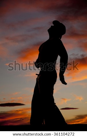 a silhouette of a cowboy leaning back and looking up in the sky.