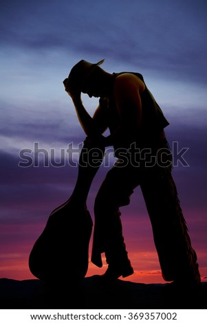 A silhouette of a cowboy leaning up against a guitar case. - stock photo
