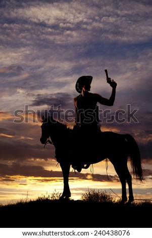 A silhouette of a cowboy on his horse holding up his pistol. - stock photo