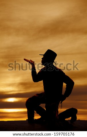 A silhouette of a cowboy on one knee blowing a kiss - stock photo
